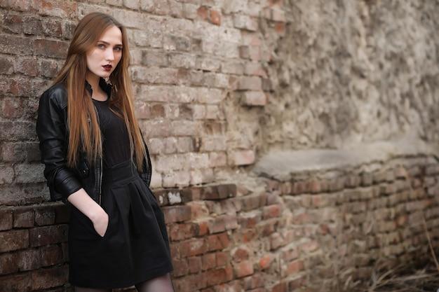 Dziewczyna idzie ulicą miasta w skórzanej kamizelce z telefonem. młoda piękna dziewczyna w kapeluszu iz ciemnym makijażem na zewnątrz. dziewczyna w stylu gotyckim na ulicy.