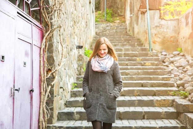 Dziewczyna idzie wąską uliczką z kamiennym brukiem. stylowa kobieta ze skórzaną torbą. schody w mieście.