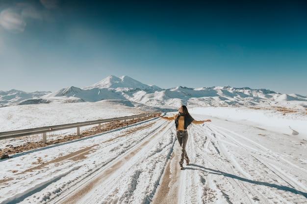 Dziewczyna idzie zaśnieżoną drogą z widokiem na góry elbrus.