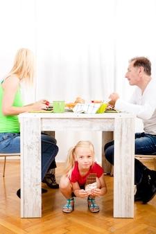 Dziewczyna je czekoladę pod stołem, podczas gdy rodzina je śniadanie