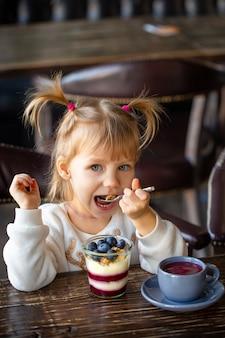 Dziewczyna je deser przy stołem. szczęśliwe dziecko je słodycze. piękne dziecko uśmiecha się do stołu. przyjęcie herbaciane z dzieckiem. zabawna dziewczyna je lody. dziecko śmieje się z lunchu. piękna dziewczyna je