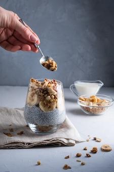 Dziewczyna je pudding chia z mlekiem kokosowym banan orzech włoski nasiona chio granola zdrowa przekąska lub br