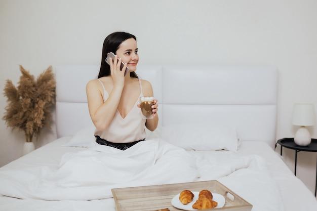 Dziewczyna je śniadanie i rozmawia przez telefon w łóżku