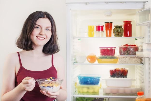 Dziewczyna je śniadanie z płatkami zbożowymi z mlekiem i jagodami przy otwartej lodówce