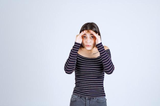 Dziewczyna jednocząc ręce na czole i patrzy w przyszłość.