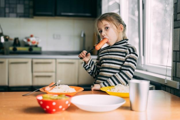 Dziewczyna jedzenie kiełbasy w kuchni bardzo apetycznie