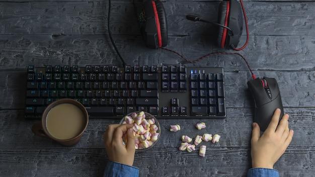 Dziewczyna jedzenie kolorowe pianki siedzi przy komputerze do gier