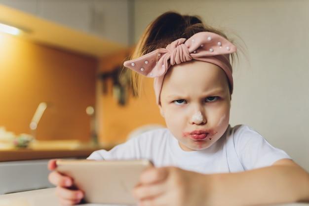 Dziewczyna jedzenie przy stole grając na telefon.