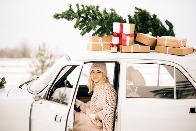 Dziewczyna jedzie retro samochodem ozdobionym choinką i przedstawia w śnieżnym lesie. koncepcja zimowej świątecznej sesji zdjęciowej