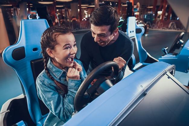 Dziewczyna jedzie samochodem w arcade. córka wygrywa.