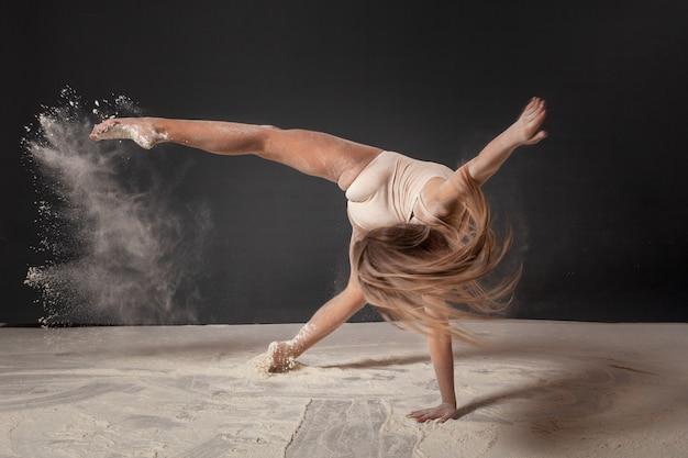 Dziewczyna jest gimnastyczką w studio na szarym bez twarzy z latającą mąką