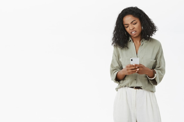 Dziewczyna jest niezadowolona trzymając smartfon patrząc z niesmakiem