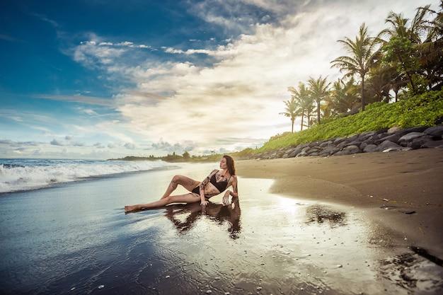 Dziewczyna jest posmarowana czarnym piaskiem i leży na plaży