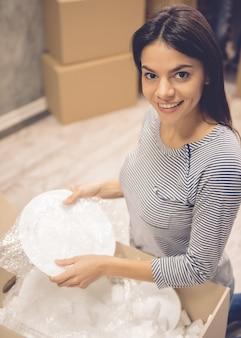 Dziewczyna jest przyglądająca kamera i ono uśmiecha się podczas pakować naczynia.
