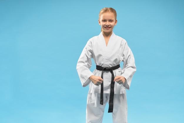 Dziewczyna jest ubranym białego kimono i czarnego pasek na błękitnym tle