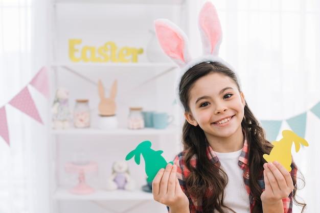 Dziewczyna jest ubranym białych królików ucho trzyma zielonego i żółtego papierowego wycinanki easter