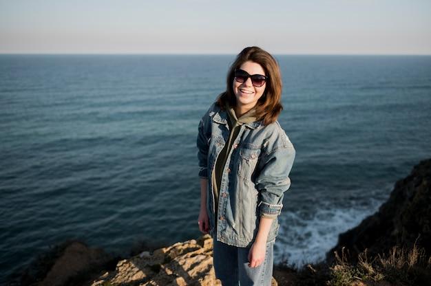Dziewczyna jest ubranym okulary przeciwsłonecznych i ocean