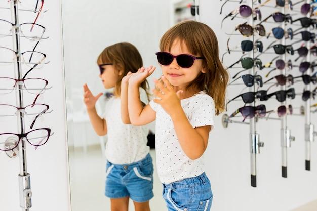 Dziewczyna jest ubranym okulary przeciwsłonecznych w sklepie