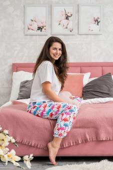Dziewczyna jest ubranym pijama pozuje na łóżku