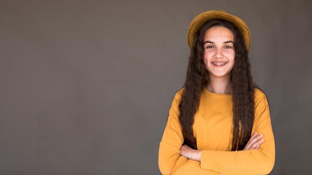 Dziewczyna jest ubranym słomianego kapelusz pozuje z kopii przestrzenią