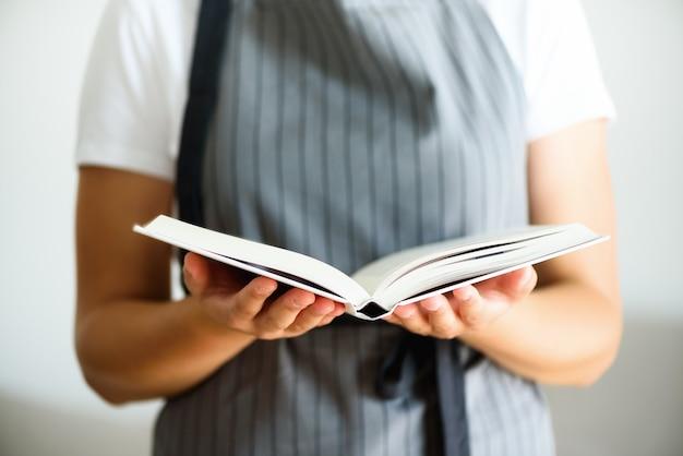 Dziewczyna jest ubranym szarego fartucha i czytelniczą książkę. koncepcja stylu życia