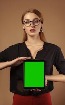 Dziewczyna jest ubranym szkła i trzyma pastylkę z zielonym pustym ekranem pionowo pastylka egzamin próbny up - technologii pojęcie -