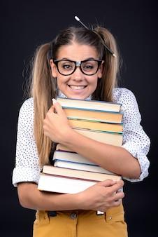 Dziewczyna jest uśmiechnięta i trzyma stos książek pod brodą.