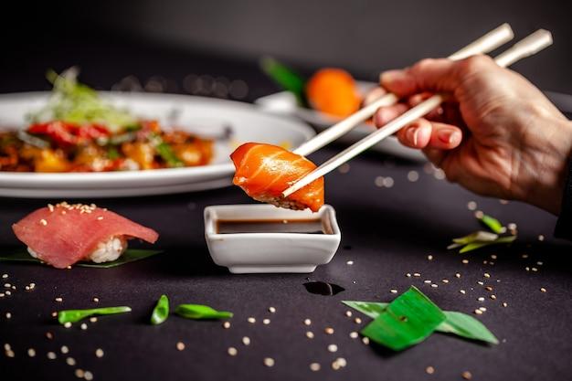 Dziewczyna jest w chińskim lub japońskim sushi restauracji.