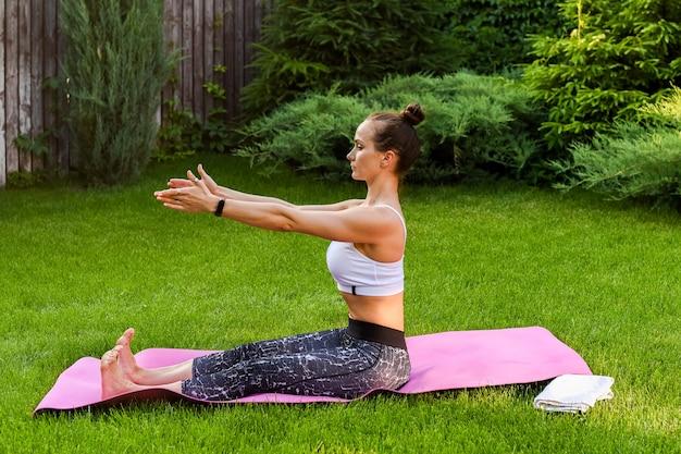 Dziewczyna jest zaangażowana w jogę w pobliżu domu. rozciąga się na plecach i monitoruje swoją postawę