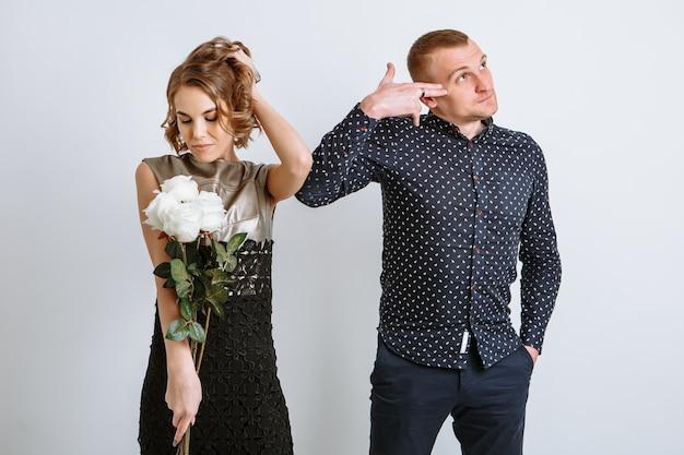 Dziewczyna jest zadowolona z prezentowanych kwiatów, młody mężczyzna robi gest, jakby strzelił sobie w głowę.