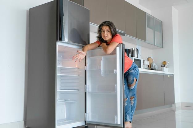 Dziewczyna jest zaskoczona pustą lodówką. brak żywności. dostawa jedzenia.