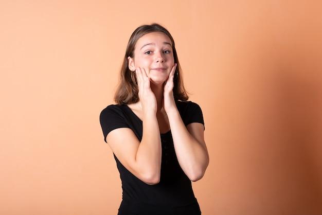 Dziewczyna jest zmartwiona i trzyma się za głowę na jasnopomarańczowym tle. w dowolnym celu.