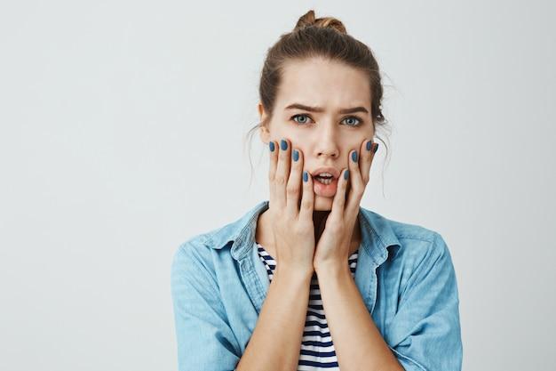 Dziewczyna jest zmartwiona i zszokowana. pracowniany portret piękna dorosła kobieta z kok fryzurą trzyma dłonie na twarzy i patrzeje z nerwowym i zmartwionym wyrazem, stoi z otwartym usta.