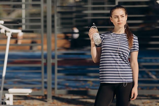 Dziewczyna jest zmęczona po treningu napoje z butelki