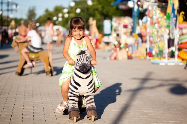 Dziewczyna jeździ na koniu zabawka w parku, zabawny szczęśliwy gestykuluje mała dziewczynka gra na koniu zabawka