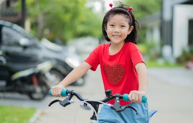 Dziewczyna jeździ na rowerze, dzieciak szczęśliwy i uśmiechnięty, azjatyckie dziecko