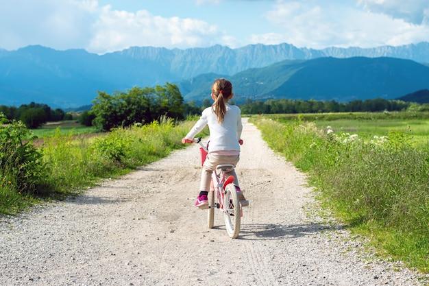 Dziewczyna jeździ różowym rowerem po pięknym górskim krajobrazie