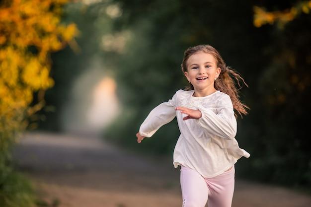 Dziewczyna junior uczennica biegnie wieczorem po drodze w parku, wesoła buźka, jasne emocje, włosy rozwijają się na wietrze.