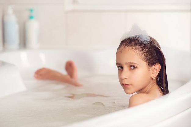 Dziewczyna kąpie się i bawi się pianką w łazience
