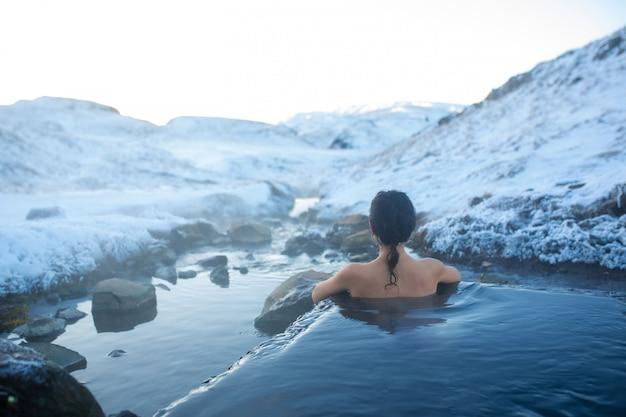 Dziewczyna kąpie się w gorącym źródle na świeżym powietrzu ze wspaniałym widokiem na zaśnieżone góry. niesamowita islandia w zimie