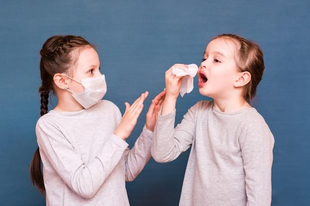 Dziewczyna kicha, chowając się za chusteczką. druga dziewczyna chroni się przed nią za pomocą maski i dłoni. zarażanie dzieci