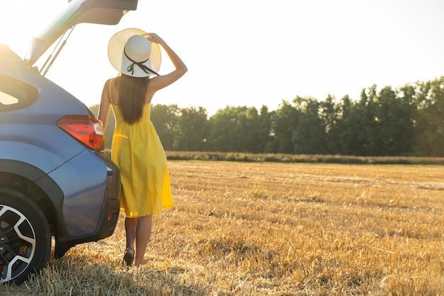 Dziewczyna kierowca w żółtej letniej sukience i słomkowym kapeluszu stojąca obok samochodu, ciesząc się ciepłym letnim dniem o wschodzie słońca. koncepcja podróży i wakacji.