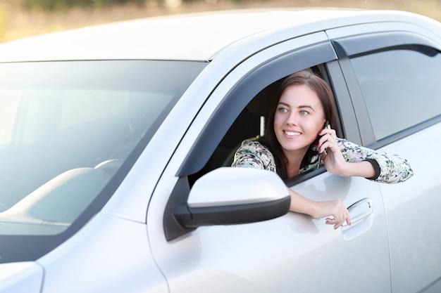 Dziewczyna kierowca z telefonem siedzi w samochodzie