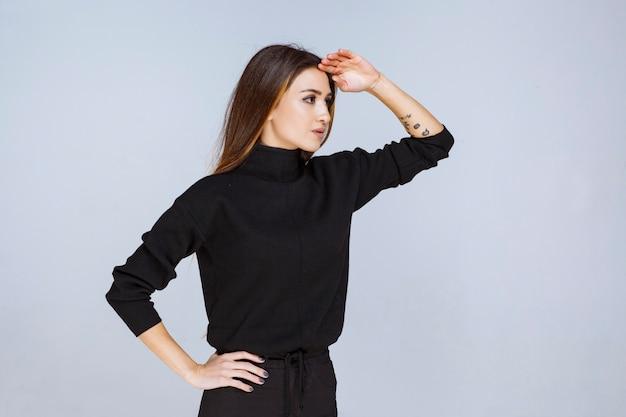 Dziewczyna kładzie rękę na jej czole i myśli. zdjęcie wysokiej jakości