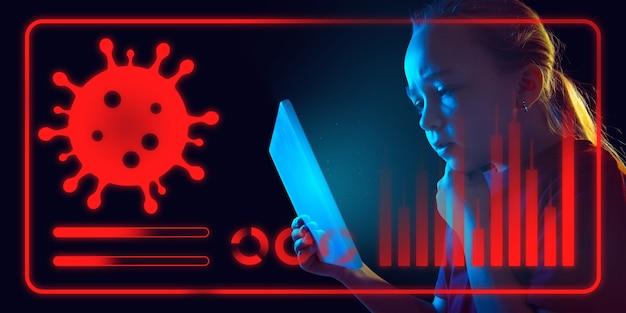Dziewczyna korzystająca z interfejsu nowoczesnej technologii i efektu warstwy cyfrowej jako informacji o rozprzestrzenianiu się pandemii koronawirusa. analizowanie sytuacji na podstawie światowej liczby przypadków, opieki zdrowotnej, medycyny i biznesu.
