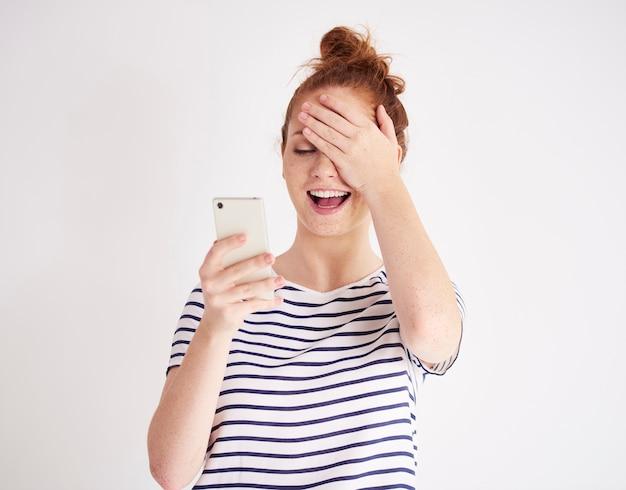 Dziewczyna korzystająca z telefonu komórkowego i śmiejącego się strzału