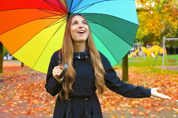 Dziewczyna korzystających z deszczowy dzień jesieni patrząc na niebo uśmiechnięty wesoły