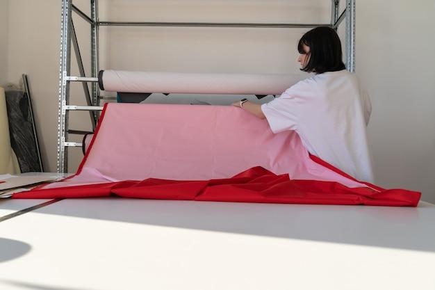 Dziewczyna krawiec przygotowuje się do cięcia tkaniny w pracowni odzieży kobieta projektantka pracuje w atelier z materiałem