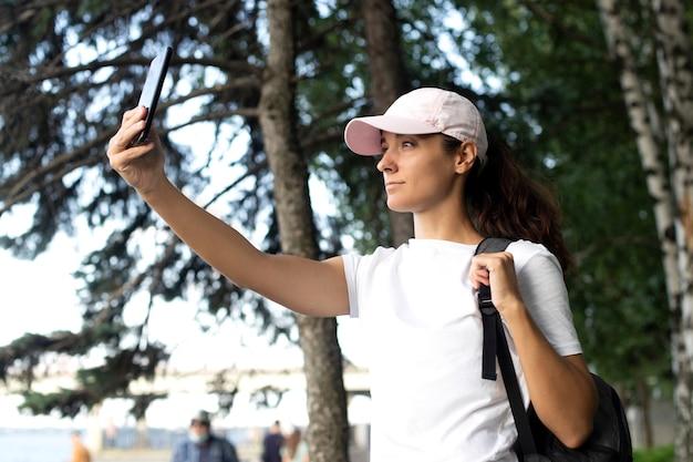 Dziewczyna kręci wideo przez telefon. młoda kobieta turysta z plecakiem i telefonem