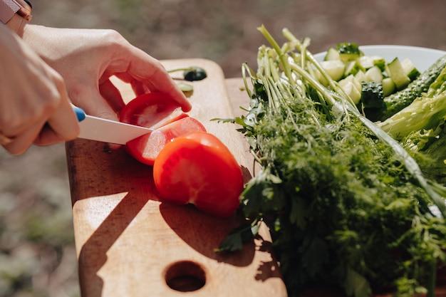 Dziewczyna kroi warzywa na desce i przygotowuje sałatkę o charakterze. słoneczny dzień i gotowanie. zamknąć widok.